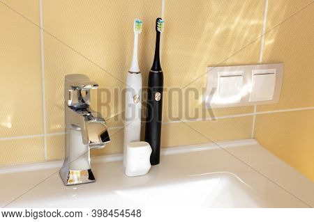 Smart Interactive Electric Sonic Toothbrushes On The Bathroom Sink, Family Set, White And Black. The