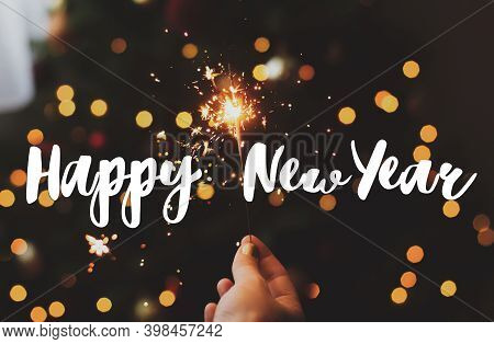 Happy New Year Greeting Card. Happy New Year Text Handwritten On Burning Sparkler In Female Hand On