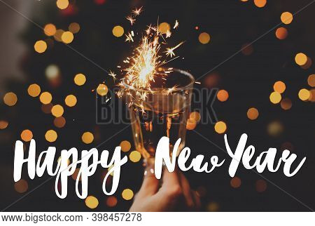 Happy New Year Greeting Card. Happy New Year Text Handwritten On Burning Firework In Champagne Glass