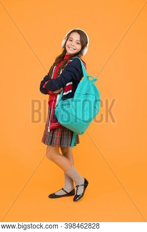 Ebook And Private Lesson Concept. Small Girl Headset With Backpack. Kid With English Flag On Jacket.