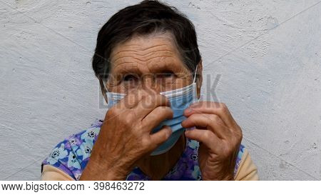 Senior Woman Of 80 Years Old Put On Protective Medical Face Mask And Fix It At Her Nose With Her Wri