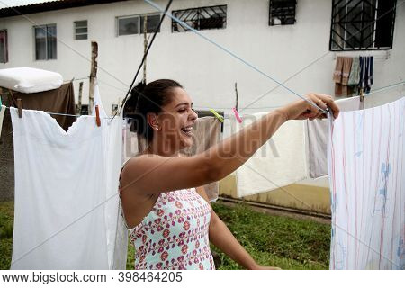Mata De Sao Joao, Bahia, Brazil - October 1, 2020: Woman Holding Clothes Washed On A Clothesline In