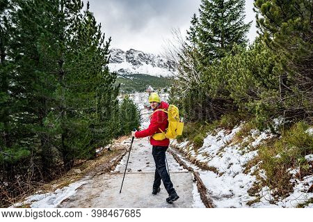 A Handsome Hiker In A Red Down Jacket, Yellow Cup And Yellow Backpack Wanders The Mountain Trail Wit