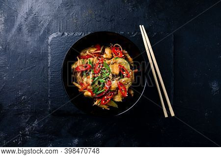 Udon Stir Fry Noodles With Chicken And Vegetables On Black Background. Hot Wok With Chicken Steaming