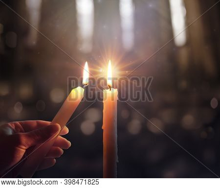 Defocused Hope Concept - Hand Igniting A Candle With Shining Flame And Blurry Lights