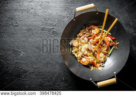 Chinese Udon Noodles In A Wok Pan With Chopsticks. On Black Rustic Background