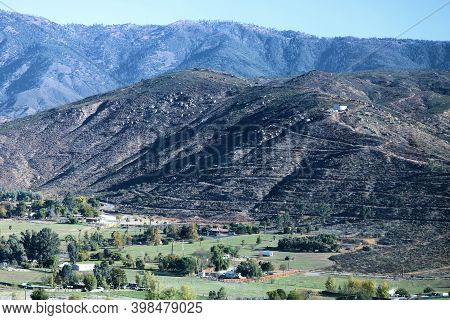 Lush Valley With Grasslands And Ranches Surrounded By Barren Mountains Covered With Chaparral Plants