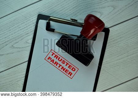 Red Handle Rubber Stamper And Trusted Partner Text Isolated On The Table.