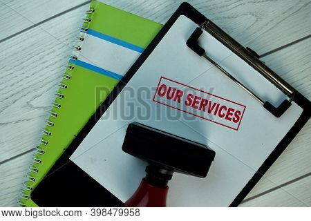 Red Handle Rubber Stamper And Our Services Text Isolated On The Table.