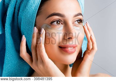 Smiling Beautiful Woman With Blue Towel On Hair And Hydrogel Eye Patches On Face Isolated On Grey
