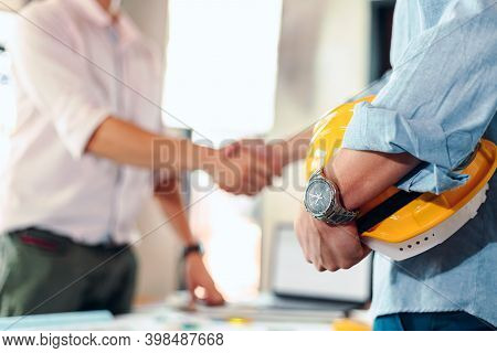 Architect Hold Safety Helmet. Blur Architect, Engineer And Businessman Handshake After Meeting Toget