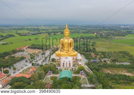 Aerial View Of The Giant Golden Buddha In Wat Muang In Ang Thong District With Paddy Rice Field Near