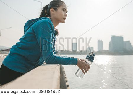 Woman Athlete Thirsty Takes A Break. She Hold Water Bottle After Running.