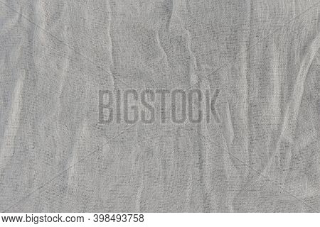 The texture of the gauze-type fabric. White thin fabric as a natural background.
