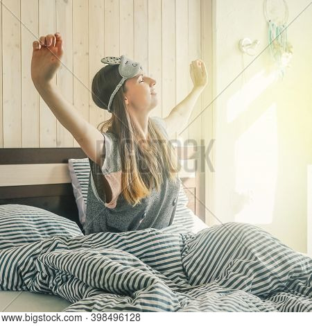 A Young Woman In Mask For Sleep Stretches As She Wakes Up From A Good Nights Sleep. Waking Up. Sun L