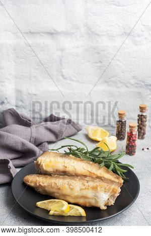 Fried Fish Hake Pollock And Slices Of Fresh Lemon. Grey Concrete Background. Copy Space.