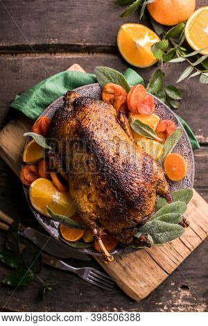 Winter Holiday Table Served For Christmas Dinner With Roasted Duck, Decorated With Orange And Herbs.