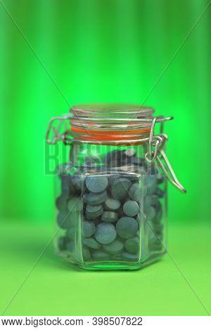 Spirulina Tablets.seaweed Supplement. Spirulina Algae Round Tablets In A Glass Jar On A Green Backgr