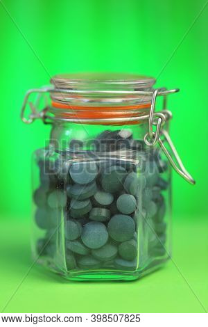 Spirulina Tablets.seaweed Supplement. Spirulina Algae Round Tablets In A Glass Jar On A Green Bright