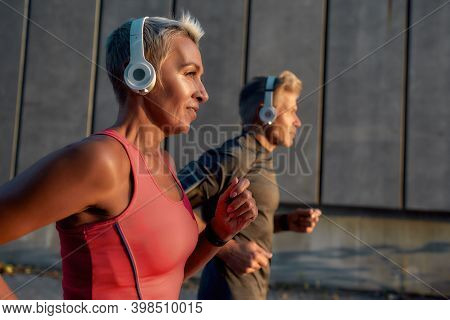 Happy And Healthy Middle-aged Couple In Headphones Running Together Through The City Street In The M