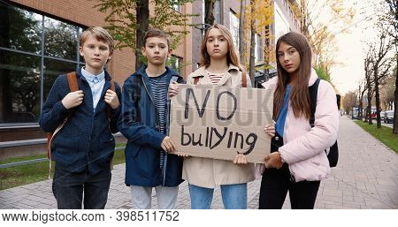 Serious Teen School Students Standing Outdoor Near School And Holding No Bullying Sign. Caucasian Bo
