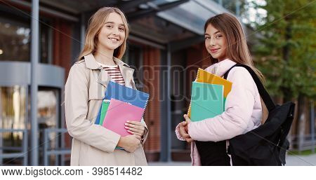 Portrait Of Cheerful Beautiful Young Girls School Students With Copybooks Standing On Street In Good