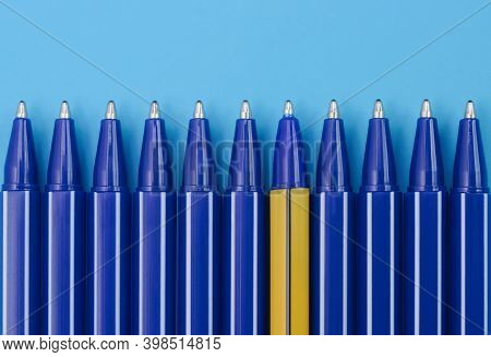 Blue Pens And One Yellow Pen On Blue Background. Top View. Difference Concept.