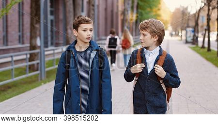 Caucasian Happy Nice Male School Students Walking On Street After School And Chatting. Portrait Of J