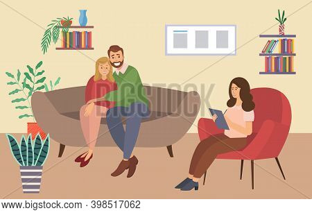 A Man And A Woman Are Sitting On A Large Brown Sofa. The Psychologist Is Sitting With A Paper And As