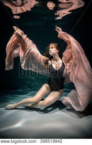 Beautiful Girl In Black Dress Underwater. Water Magic. Underwater Photography. Art