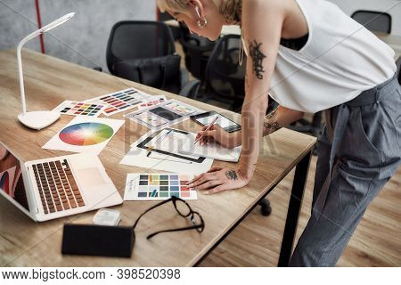 Young Blonde Tattooed Female Designer Making Some Sketches While Standing Near Office Desk. Working