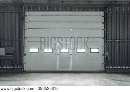 Overhead Sectional Door In A Large Industrial Building. Lift Gate. Inside View.
