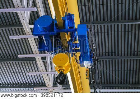 Overhead Traveling Cathead With Steel Hooks In Industrial Engeenering Plant Shop. Steel Slings. Side