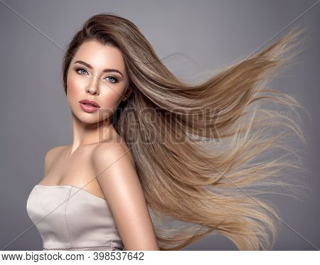 Young woman with long straight hair. Sexy and gorgeous blonde woman. Portrait of an attractive female posing at studio. Closeup face of a beautiful girl with makeup smoky eyes.