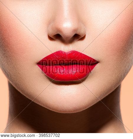 Woman lips with a red lipstick on lips. Closeup female red lips.  Bright makeup.