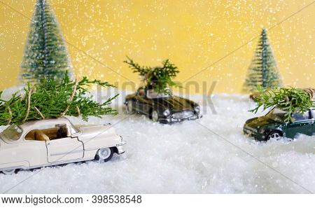 Toy Cars In The Forest Among The Snowdrifts That Are Delivers Christmas Trees. Blurred Background. M