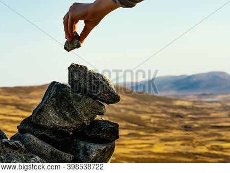 Hand Placing A Rock On Top Of A Cairn On The Peak Of A Mountain. Close Up.