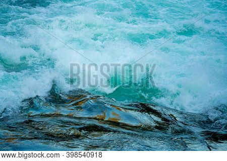 Wild River Rapids In A Glacial River With White Foam And Splashing Water. Close Up.