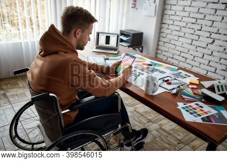 Young Male Ux Ui Designer In A Wheelchair Choosing Color Samples For New Project While Working At Hi