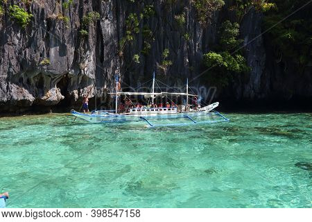Palawan, Philippines - December 1, 2017: Tourists Ride Outrigger Bangka Boat On Island Hopping Tour