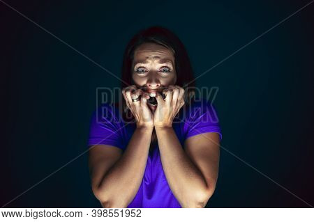 Hiding. Portrait Of Young Crazy Scared And Shocked Caucasian Woman Isolated On Dark Background. Copy