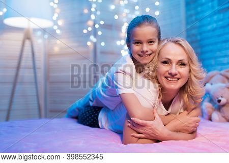 Little Girl Sitting On The Bed And Reading A Big Book. Little Girl Looks In A Book While Sitting Sur