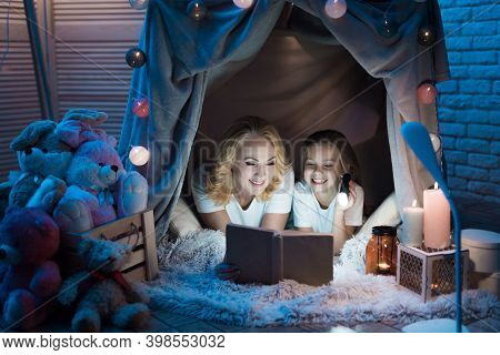 Grandmother And Granddaughter Are Reading Book In Blanket House With Flashlight At Night At Home. Gr