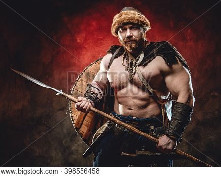 Nude Handsome Northern Barbarian With Naked Torso And Muscular Build Poses Holding A Spear In Dark R