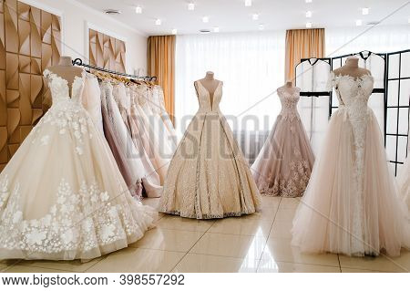 Beautiful Wedding Dresses, Bridal Dress Hanging On Hangers And Mannequin In Studio. Fashion Look. In
