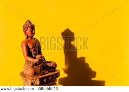Jade Buddha, Buddha Figurine On A Yellow Background, Shadow Of The Buddha In The Sun