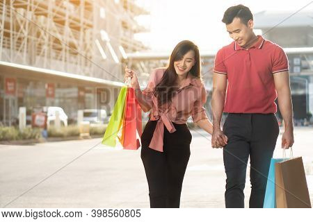 Happy Young Couple Of Shoppers Walking In The Shopping Street Towards And Holding Colorful Shopping