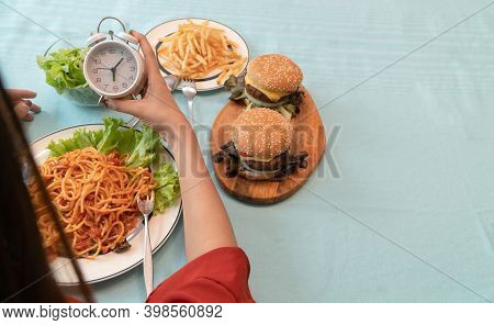 Young Woman Holding Clock And Ready To Eating A Hamburger, French Fries, And Spaghetti For Breakfast