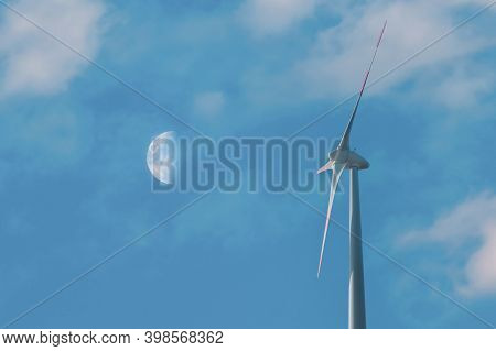 Wind Turbine On Blue Sky With Moon Background. Wind Turbine Close-up Producing Clean And Renewable E