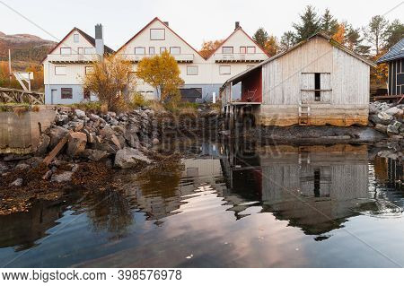 Traditional Norwegian Fishing Village Landscape, Wooden Barns Stand On The Sea Coast. Snillfjord, So
